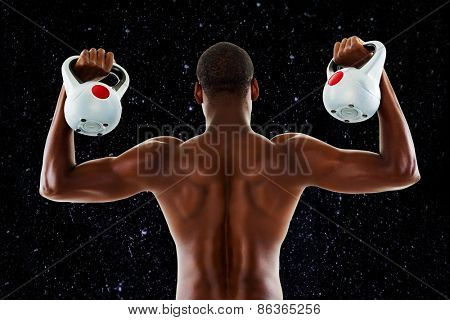 Rear view of shirtless fit man lifting kettle bells against black background