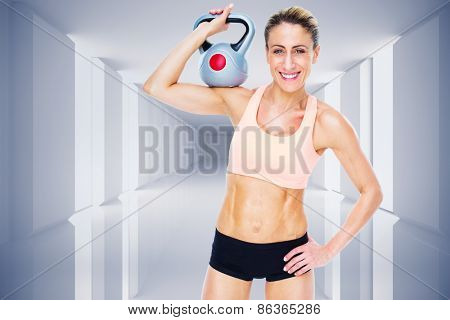 Female blonde crossfitter holding kettlebell smiling at camera against digitally generated room
