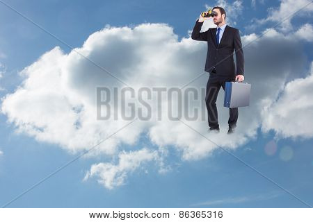 Businessman looking through binoculars holding briefcase against cloudy sky