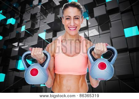 Smiling female crossfitter lifting kettlebells against blue and black tile design