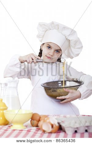 Little girl cook whips whisk eggs in a large plate, isolated on white background