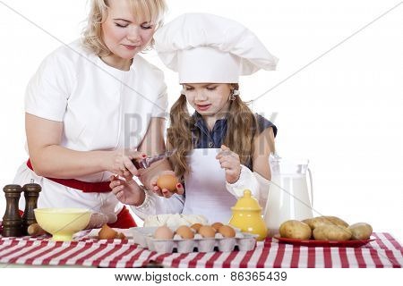 Little girl helping her mother prepare a cake, isolated on white background