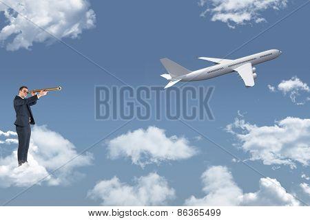 Businessman looking through telescope against blue sky