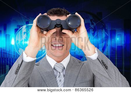 Businessman holding binoculars against global business graphic in blue