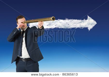 Businessman looking through telescope against cloud arrow