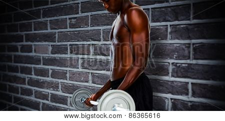 Determined fit shirtless young man lifting barbell against red brick wall