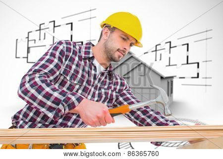 Handyman using hammer on wood against house in grey with architect plans