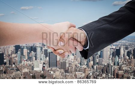 Close up of a handshake against new york