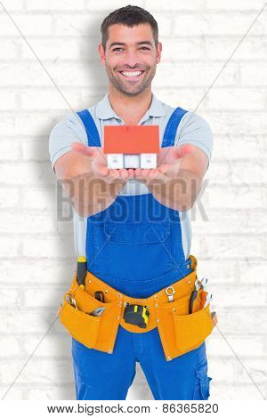 Portrait of happy construction worker holding house model against white wall