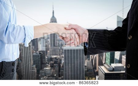 Close up of a business people closing a deal against new york
