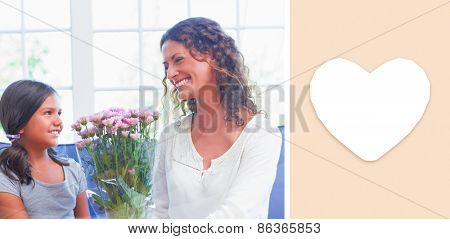 heart against happy mother and daughter sitting on the couch with flowers