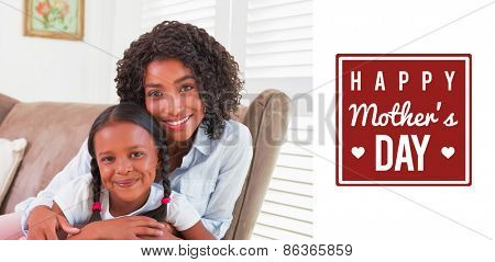 mothers day greeting against pretty mother sitting on the couch with her daughter smiling at camera