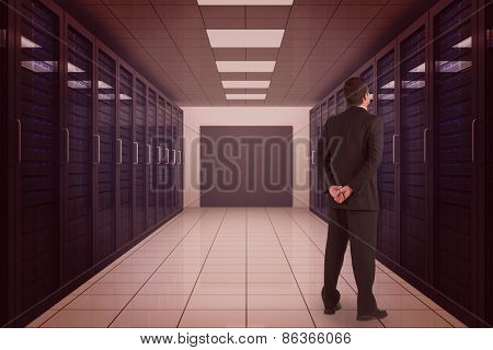 Businessman standing and looking against server room with towers