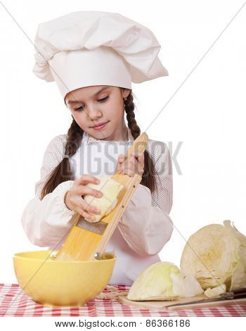 Portrait of a little girl in a white apron and chefs hat shred cabbage in the kitchen, isolated on white background