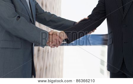 Handshake in agreement against wall street