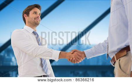 Young businessmen shaking hands in office against room with large window looking on city