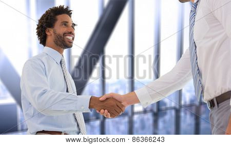 Two businessmen shaking hands in office against room with large window looking on city