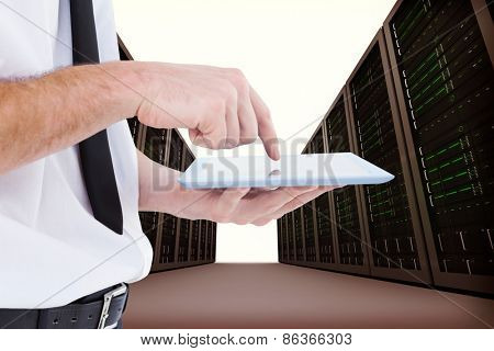 Businessman scrolling on his tablet pc against server hallway