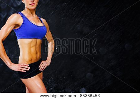 Female bodybuilder against black background