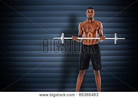 Portrait of a serious fit young man lifting barbell against grey shutters