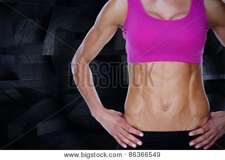 Female bodybuilder posing with hands on hips mid section against dark room