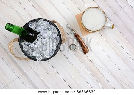 Overhead shot of an ice bucket with an opened beer bottle, a mug of beer and opener on a rustic white wood table. Horizontal format with copy space.