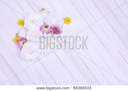 A group of Spring flowers on a wood table. Overhead shot with intentional soft focus and high key effects applied. Horizontal format with copy space.