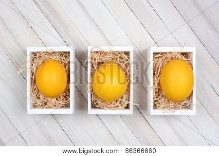 High angle shot of three wooden boxes each with a single lemon on a bed of straw. The wooden crates are on a rustic wood table.