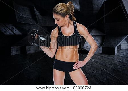Female bodybuilder holding large black dumbbell with arm up looking at bicep against dark room