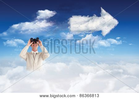 Confident businessman with binoculars against cloud arrow