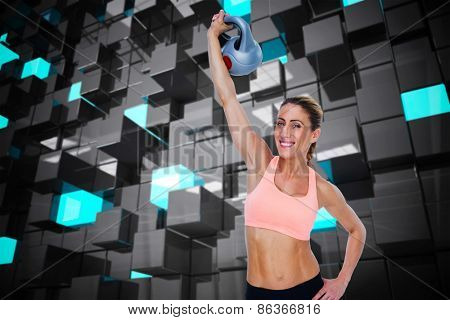 Female blonde crossfitter lifting kettlebell above head smiling at camera against blue and black tile design