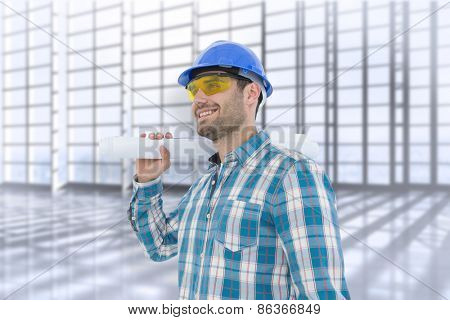 Smiling architect looking away while holding blueprint against room with large window overlooking city