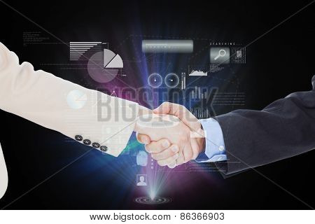 Smiling business people shaking hands while looking at the camera against technology interface