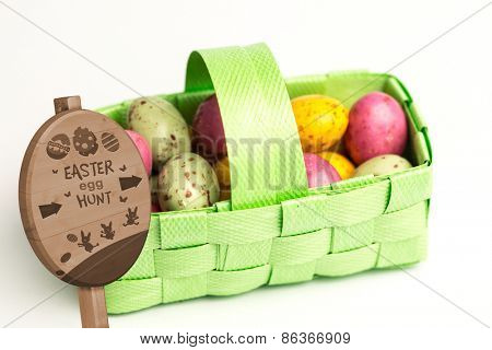 Easter egg hunt sign against speckled colourful easter eggs in a green basket