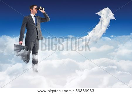 Businessman looking through binoculars against cloud arrow