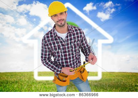 Smiling handyman holding tape measure against green light bulb with white house outline