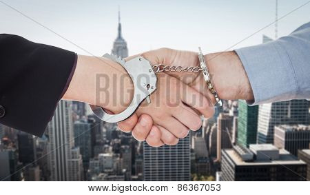Business people in handcuffs shaking hands against new york