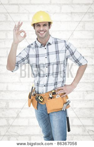 Handyman gesturing OK sign against white wall