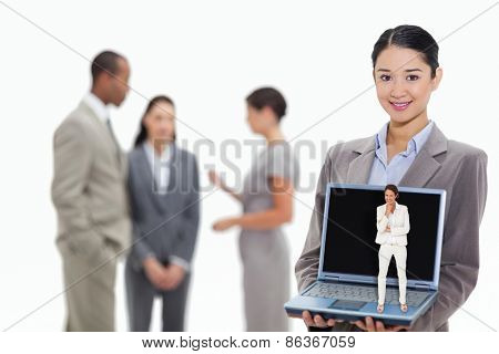 Thinking businesswoman against businesswoman smiling showing a laptop screen with coworkers in the background
