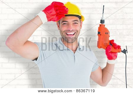 Smiling manual worker holding drill machine against white wall