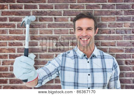 Happy handyman holding hammer against red brick wall