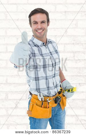 Happy handyman gesturing thumbs up against white wall
