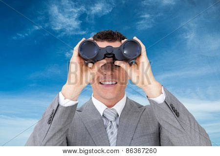 Businessman holding binoculars against blue sky