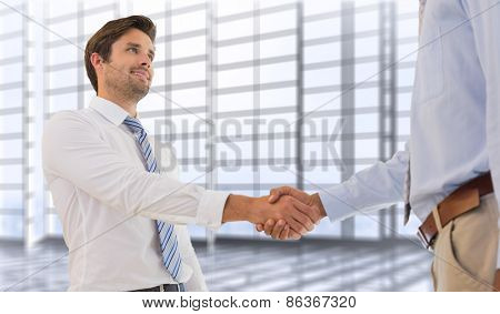Young businessmen shaking hands in office against room with large window overlooking city