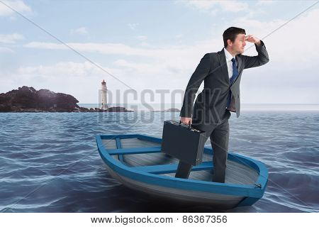 Businessman in boat against calm sea with lighthouse