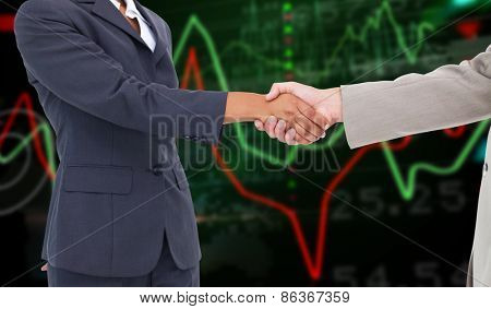 Side view of hands shaking against stocks and shares on black background