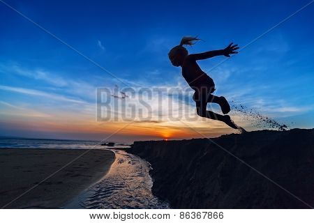 Girl jumping on the sunset beach