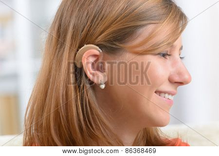Young, smiling woman wearing deaf aid