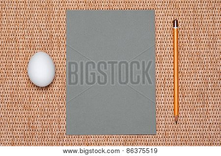 Gray Paper And Pencil And Egg On Background