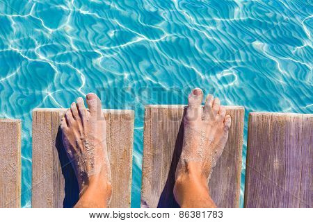 sandy feet on the pier under tropical turquoise water sea ocean